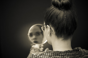 this woman is reflecting on herself by looking in the mirror